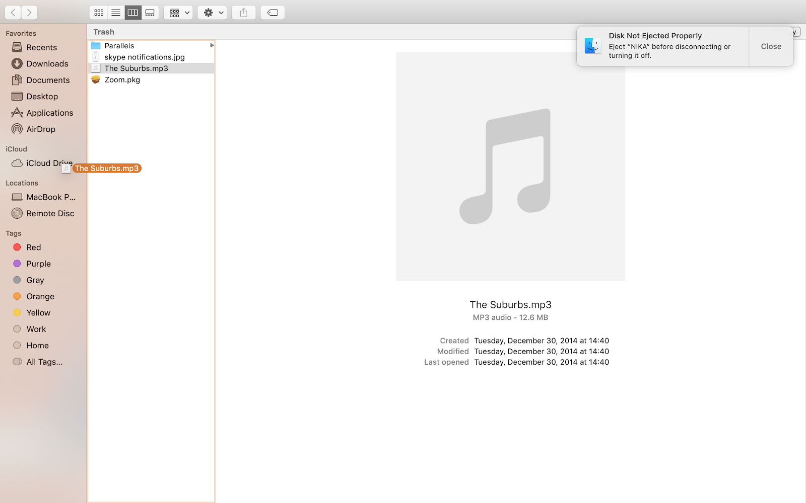 a finder window open in the trash folder displaying an mp3 file being dragged towards the iCloud drive folder
